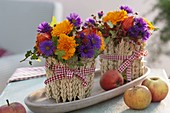 Small Thanksgiving bouquets in wheat-clad glasses
