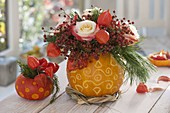Decorative carved pumpkins (cucurbita) as vases for pink