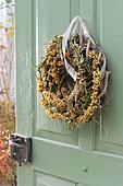 Door wreath of sea buckthorn on blank of dry tendrils