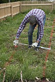 Garden planning, man measuring path width and recording it with color powder