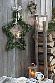 Star made of mixed coniferous green with lantern on board wall