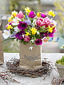 Colorful spring bouquet in paper bag with inscription