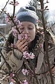 Woman enjoys the scent of Viburnum bodnantense 'Dawn'
