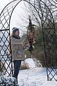 Woman filling homemade feeding station out of Cornus branches