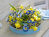 Wicker wreath with primroses and narcissus