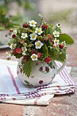 Small forest and strawberry bouquet in jug with strawberry decor