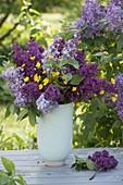 Fragrant bouquet of light and dark syringa with ranunculus