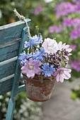 Small meadow bouquet in clay pot hanged on chair back