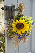 Thanksgiving bouquet on the door handle with helianthus, wheat