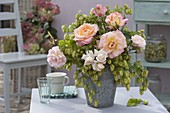Pink (rose) and humulus (hops) bouquet in zinc vase
