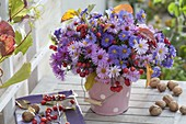 Autumn bouquet in metal bucket with aster and malus