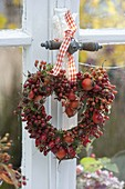 Heart made of roses (rosehip) with moss on the window