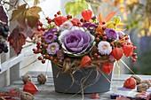 Autumn arrangement in metal jardiniere with Brassica, Physalis