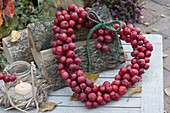 Heart of ornamental apples leaning against firewood, small glass as a lantern
