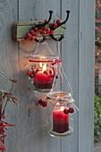 Old preserving jars hung on coat hooks as lanterns