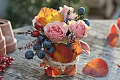 Small autumn bouquet with pink (rose, rosehips), sloe