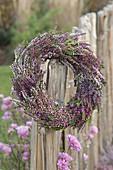 Kranz aus Calluna vulgaris (Knospenbluehender Besenheide) an Zaun