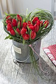 Valentine's bouquet made of red tulips in grass-heart