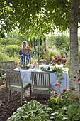 Table laid in the flower garden under walnut tree