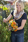 Woman picking summer flowers bouquet with edible flowers