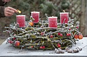 Advent wreath of mossy branches on metal frame with candle holders