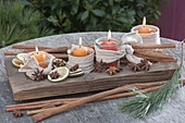 Small glasses with knitted ribbon on a wooden tray as an unusual Advent wreath