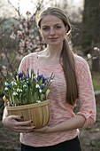 Woman carrying woodchip basket with Galanthus nivalis and Iris