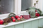 Windowsill decorated with red balls, lanterns, cones, moss, ivy