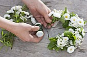 Tying a wreath of daisies and herbs