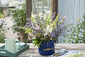 Bouquet made of early summer perennials in blue enamel bucket