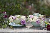 Glasses as lanterns in cereal bowls with rose flowers