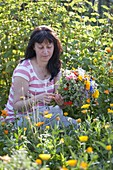 Woman picking bouquet from everything that blooms in the cottage garden