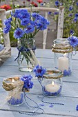 Rural table decoration with preserving jars as lanterns