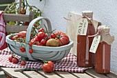 Woodchip basket with freshly picked tomatoes and bottles with sugo