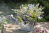 Bouquet of herb blossoms in watering can