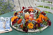Wreath made of edible flowers and herbs with preserving jar as a lantern
