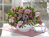 Violet-pink spring arrangement with insertion aid in soup tureen