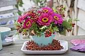 Autumn bouquet on terrace table, Zinnia (Zinnia), branches