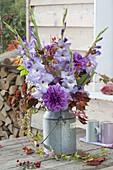 Violet bouquet in old zinc milk jug, dahlia, gladiolus