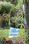 Hanging armchair on the tree, flower beds with summer flowers and perennials