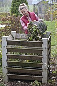 Woman placing garden waste into the compost bin