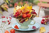 Small autumn bouquet in cup on coaster