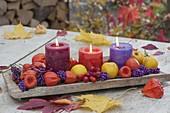 Holz-Brett mit Kerzen, dekoriert mit Physalis (Lampions) , Chaenomeles