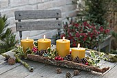 4 yellow candles in bark, decorated with ilex, red berries