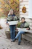 Kinder mit Metall-Jardinierer mit Calluna vulgaris Garden Girls
