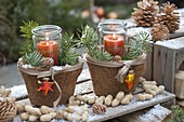 Preserving jars as lanterns in coconut pots, decorated with twigs