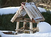 Bird feeder house in the snow with blackbird, tit dumpling