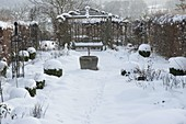 Snow-covered rose beds, Buxus in ball shape, hedge, gazebo