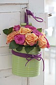 Bouquet made of roses in green tin box with handle on door