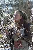 Woman sniffs at almond blossoms